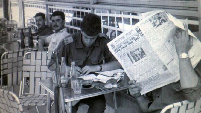 """מדינה של רדיו ועיתונים. חיילים בבית קפה עם """"ידיעות אחרונות"""", תקופת ההמתנה שלפני מלחמת ששת הימים. שימו לב לשמשות המודבקות בנייר דבק נגד הדף (צילום: ארכיון צה""""ל)"""