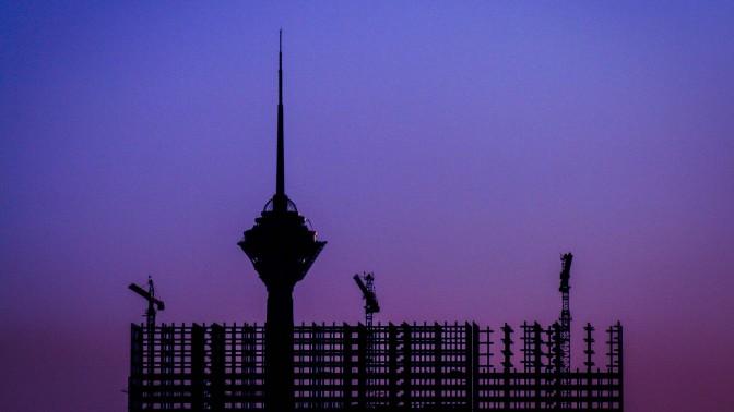 מגדל התקשורת מילאד מציץ מעל נוף פיגומים ומנופים בטהראן, איראן (צילום: Mohammadali F, רשיון cc-by-nc-sa)