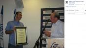 """יו""""ר האגודה לזכות הציבור לדעת, פרופ' אלי פולק, מעניק תעודת הוקרה לזליג רבינוביץ'. ספטמבר 2013 (צילום מתוך עמוד הפייסבוק של האגודה)"""