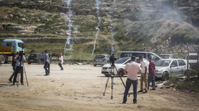 עיתונאים פלשתינים בהפגנה ליד כלא עופר למען שחרורו של העיתונאי עומאר נזאל, נמלטים מרימוני גז שנורו בידי כוחות ישראלים. 26.4.16 (צילום: פלאש 90)