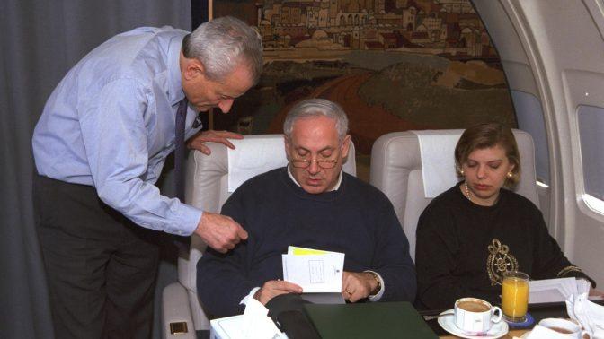 """ראש הממשלה בנימין נתניהו בשיחת עבודה עם יועצו דוד בר-אילן, בטיסה לביקור בוושינגטון. מימין: שרה נתניהו, 19.1.1998 (צילום: יעקב סער, לע""""מ)"""