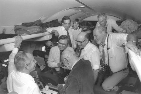 """ראש הממשלה שמעון פרס משוחח עם אנשי התקשורת המלווים אותו בטיסה לביקור בארה""""ב, 16.10.1985. מימין: דוד רובינגר (צילום: חנניה הרמן, לע""""מ)"""