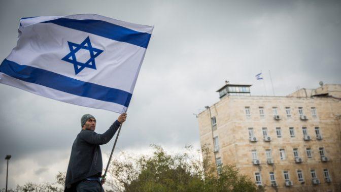 מפגין על רקע בניין משרד ראש הממשלה בירושלים, 2017 (צילום: יונתן זינדל)