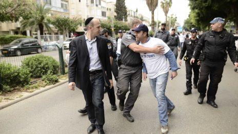 """עובד של רשות השידור מאיים על כתב המדיה של """"דה-מרקר"""", נתי טוקר, במהלך הפגנה של עובדי הרשות נגד סגירת הרשות, תל-אביב, 21.3.17 (צילום: תומר נויברג)"""