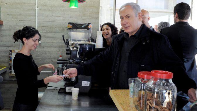 """בנימין נתניהו משלם לעובדת בבית-הקפה בפארק אריאל שרון, חירייה. 20.1.11 (צילום: משה מילנר, לע""""מ)"""