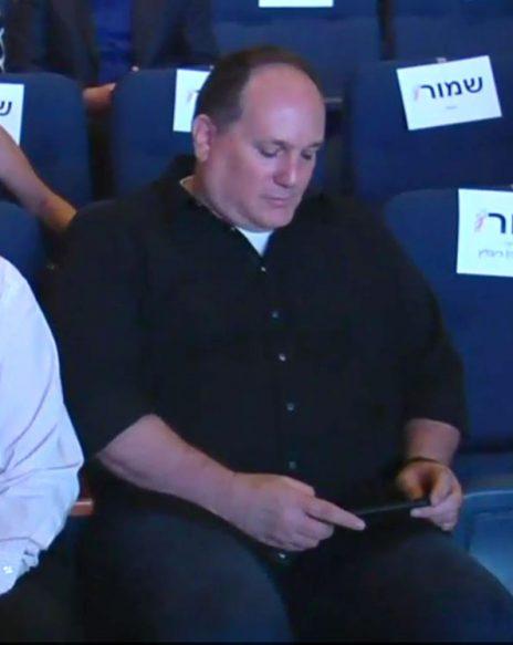 """רון ירון, העורך הראשי של """"ידיעות אחרונות"""", מחזיק במכשיר טלפון נייד (צילום מסך)"""