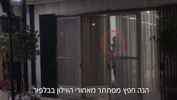 """ניר חפץ מסתתר מאחורי וילון במעון ראש הממשלה, חמישה ימים לפני שנעצר (צילום מסך מתוך """"אולפן שישי"""")"""