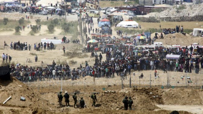 """מפגינים פלסטינים וחיילי צה""""ל משני עברי הגבול, רצועת עזה, 13.4.18 (צילום: סאלימן חאדר)"""