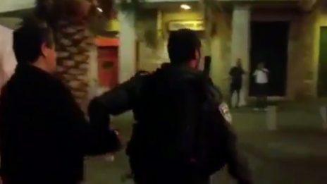 שוטר מוביל את ג'עפר פרח למעצר, כשהוא אזוק והולך על רגליו, 18.5.18 (צילום מסך: MSN)