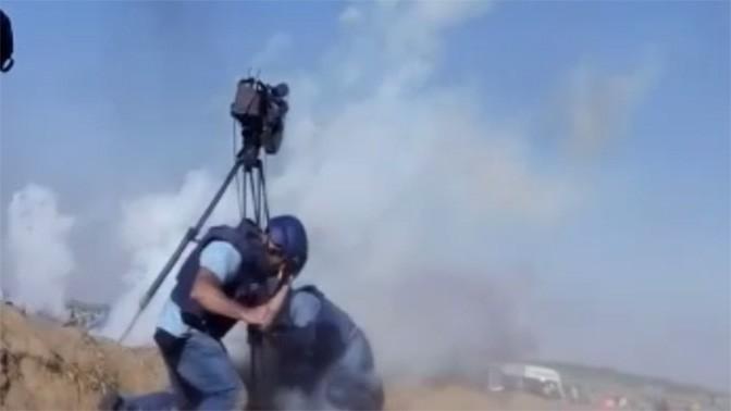 עיתונאים נמלטים מרימוני גז ששוגרו מכלי טיס בלתי מאויש בעת סיקור ההפגנות בגבול הרצועה, 14.5.18 (צילום מסך מסרטון אל-ג'זירה)