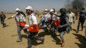 פלסטינים מפנים את צלם העיתונות הפצוע מוחמד אלת'לאת'יני במהלך הפגנות ליד הגבול של רצועת עזה, 11.5.2018 (צילום: עבד רחים ח'טיב)
