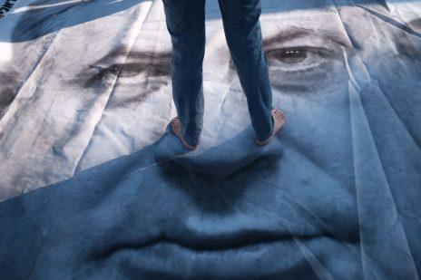 """אשה עומדת על דיוקנו של ראש הממשלה בנימין נתניהו בהפגנה נגד """"חוק הלאום"""", 30.7.2018 (צילום: תומר נויברג)"""