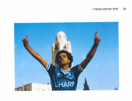 """הצילום של משה שי שבו נראה אלי אוחנה מניף את ידיו על רקע מגדל ימק""""א, כפי שצורף לכתב התביעה"""