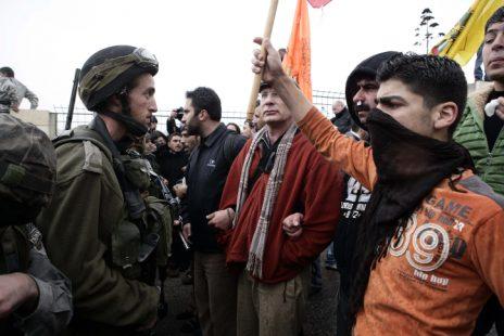 """פעילי שלום ישראלים ופלסטינים עומדים מול חיילי צה""""ל בחברון, 2010 (צילום: אביר סולטן)"""
