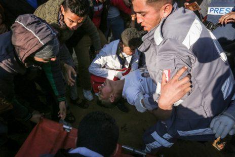 מפגינים מפנים עזתי שנפצע בהפגנה ליד רפיח, 19.4.19 (צילום: עבד רחים ח'טיב)