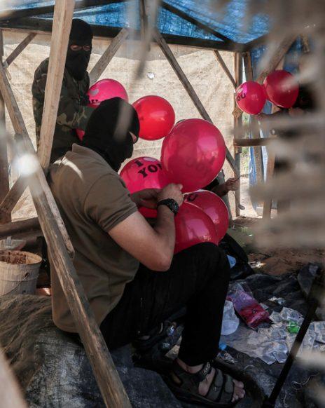 רעולי פנים פלסטינים מכינים בלוני תבערה. רצועת עזה, 25.6.2019 (צילום: חסן ג'די)