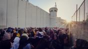 פלסטינים מחכים במחסום ליד גדר ההפרדה (צילום: פלאש 90)