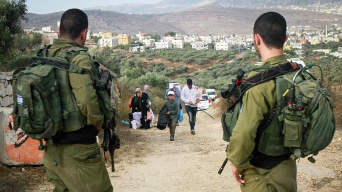 חיילים ישראלים משקיפים על פלסטינים בצאתם למסיק זיתים ליד הכפר סאלם שבגדה המערבית. 15.10.2019 (צילום: נאסר אישתיה)