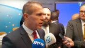 """גלעד ארדן, השר לנושאים אסטרטגיים, מדבר בשולי מסיבת העיתונאים בבריסל. מאחוריו: הרב מנחם מרגולין (צילום מסך מתוך שידורי """"ערוץ 7"""")"""