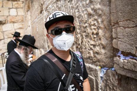 תייר אמריקאי עוטה מסכה בכותל המערבי, 27.2.2020 (צילום: אוליבייה פיטוסי)