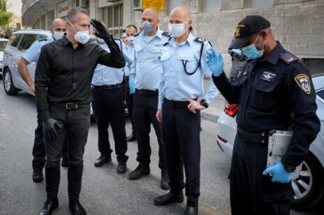 השר לבטחון הפנים, גלעד ארדן, מצדיע לשוטר. ירושלים, 7.4.2020 (צילום: אוליבייה פיטוסי)