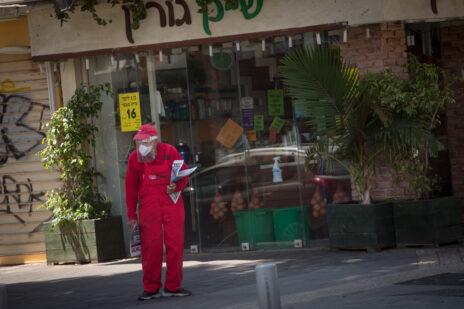 """מחלק עיתונים של """"ישראל היום"""" בתל-אביב, בעיצומה של מגפת הקורונה. 14.4.2020 (צילום: מרים אלסטר)"""