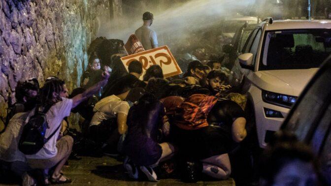 מפגינים תופסים מחסה מפני זרנוקי המשטרה בהפגנה נגד נתניהו בירושלים. 23.7.2020 (צילום: נעם ריבקין-פנטון)