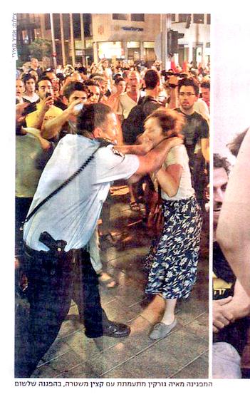 """""""המפגינה מאיה גורקין מתעמתת עם קצין משטרה, בהפגנה שלשום"""". """"מעריב"""", 25.6.2012"""