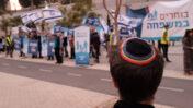 """יהודי חובש כיפת גאווה מתבונן על הפגנת פעילים נגד זכויות להט""""בים, תל-אביב, 2018 (צילום: תומר נויברג)"""