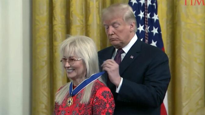 """נשיא ארה""""ב דונלד טראמפ עונד את מדליית החירות לצווארה של ד""""ר מרים אדלסון, הבעלים של """"ישראל היום"""" (צילום מסך)"""