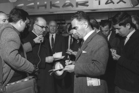 """איתן הבר (מימין, עם שפם) רושם דברים מפיו של ראש הממשלה לוי אשכול לפני צאתו לביקור מדיני בלונדון, 1965 (צילום: פריץ כהן, לע""""מ)"""