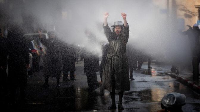 """מפגין חרדי סופג מים ממכת""""זית משטרתית. ירושלים, 26.1.2021 (צילום: יונתן זינדל)"""