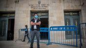 """מאבטח מחוץ לבית המשפט המחוזי בירושלים, ביום פתיחת משפטם של ראש הממשלה בנימין נתניהו והמו""""לים נוני מוזס ושאול ואיריס אלוביץ', בעבירות שחיתות; 24.5.2020 (צילום: יונתן זינדל)"""