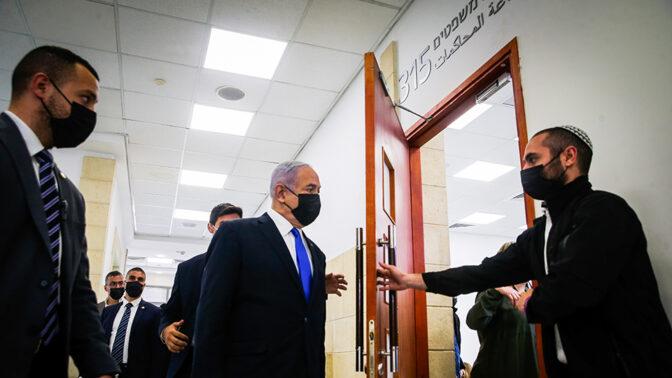 """ראש ממשלת ישראל, בנימין נתניהו, נכנס לאולם בית-המשפט המחוזי בירושלים ליום הראשון בשלב העדויות של משפטו הפלילי, שבו הוא נאשם בקבלת שוחד מהמו""""ל שאול אלוביץ' ובכריתת עסקה מושחתת עם המו""""ל נוני מוזס, 5.4.2021 (צילום: אורן בן-חקון)"""