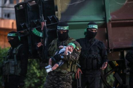 שלושה חברים בארגון הטרור גדודי עז א-דין אל-קסאם, בידיהם תינוק, במצעד צבאי בחאן-יונס. 27.5.2021 (צילום: עבד רחים חטיב)