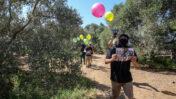 רעולי פנים פלסטינים שהתמקצעו בהפרחת בלוני תבערה מציגים בלונים עם עלוני תעמולה שישוחררו משטח רצועת עזה לישראל. 4.9.2021 (צילום: עטייה מוחמד)